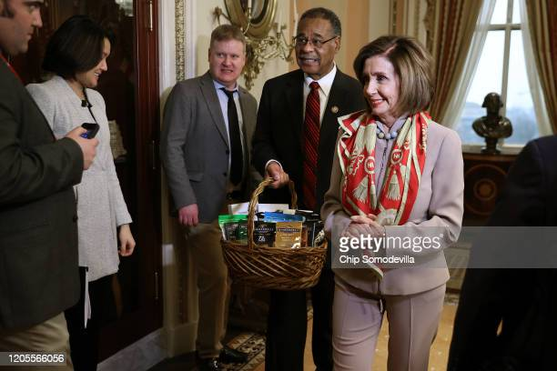 Journalists look on as Speaker of the House Nancy Pelosi presents Rep Emanuel Cleaver with a basket with items from the San Francisco area including...