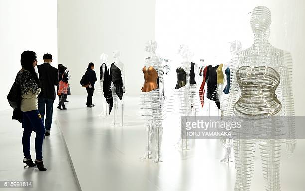 Journalists looks at creations by Japanese designer Issey Miyake during a press preview of the Miyake Issey Exhibition at the National Art Center in...