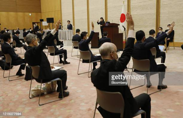 Journalists maintaining social distancing raise their arms to ask questions during a news conference in Tokyo, Japan, on Monday, May 25, 2020. The...