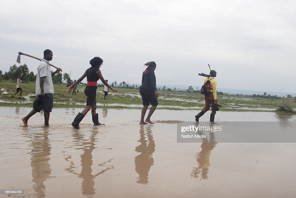 Journalists make their way through flood waters on April 1, 2013 in Kisumu County, Kenya. Thousands of people have been displaced by the heavy rains with houses destroyedand livestock lost. At least 10 people have reportedly been killed by the floods.