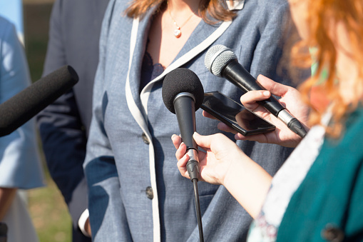 Journalists making media interview with businesswoman or female politician 1062830760