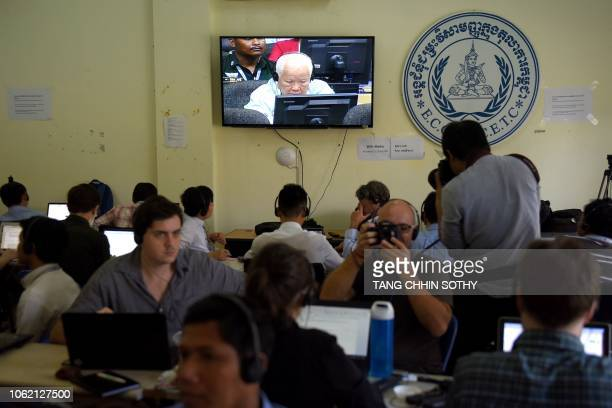 Journalists observes the verdict of former Khmer Rouge leader Khieu Samphan shown on a live video broadcast in the press room of the Extraordinary...