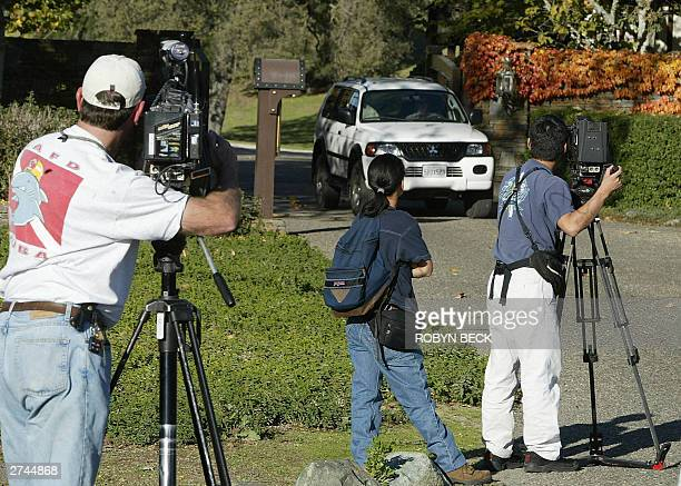 Journalists photograph a car leaving the main entrance to pop star Michael Jackson's estate known as Neverland Ranch 19 November 2003 in Los Olivos...