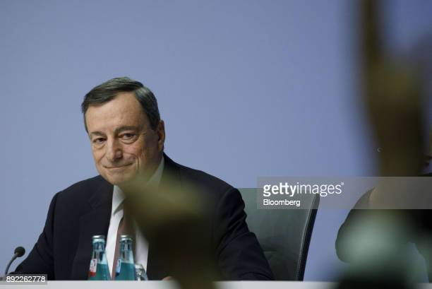 Journalists raise their hands to ask questions as Mario Draghi president of the European Central Bank looks on during a news conference following the...