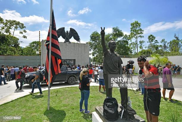 Journalists remain near the flag of Brazilian football club Flamengo placed at half mast at the team's training center after it caught fire in Vargem...