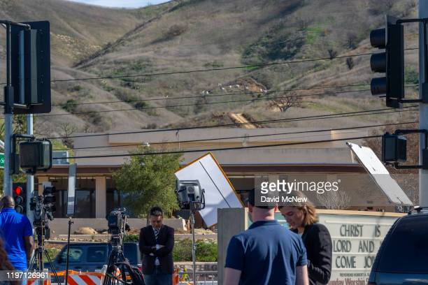 Journalists report from a parking lot of the Church In the Canyon as investigators on a distant hill work at the scene of the helicopter crash, where...