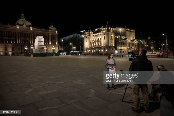 Journalists report from downtown Belgrade on March 18 as Serbia has introduced curfew from 8 pm to 5 am for entire population except those authorised...