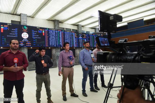 Journalists report from the trading floor at the Pakistan Stock Exchange in Karachi on March 9 2020