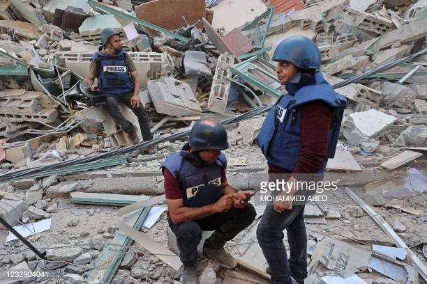 Journalists sit on to the rubble of Jala Tower, which was housing international press offices, following an Israeli airstrike in the Gaza Strip on...