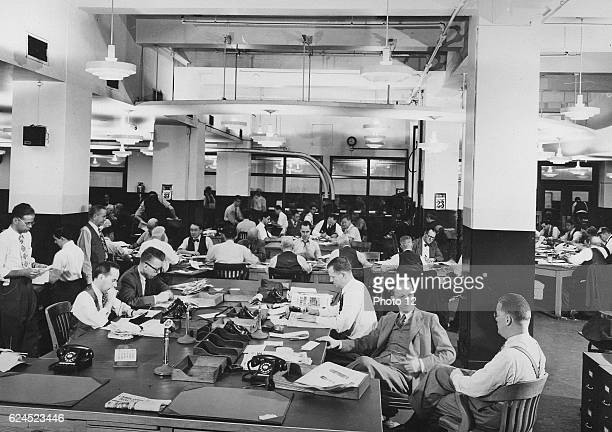 Journalists sitting in a news room at an American newspaper office circa 1945