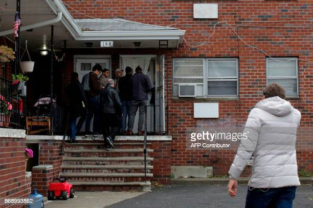Journalists speak with a neighbor after an FBI raid next to the unit where suspect Sayfullo Saipov's had his apartment on November 1 in Paterson New...