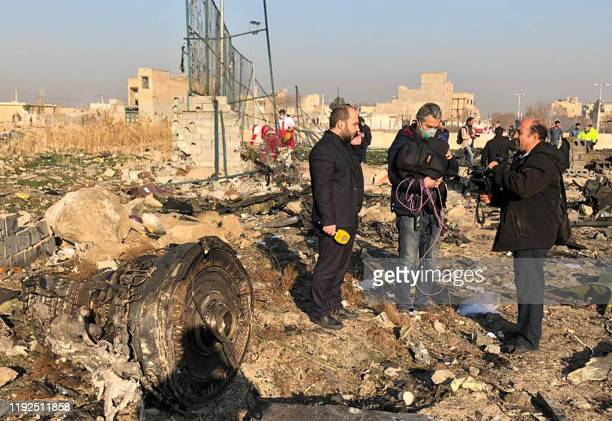 TV journalists stand amid the wreckage after a Ukrainian plane carrying 176 passengers crashed near Imam Khomeini airport in the Iranian capital...