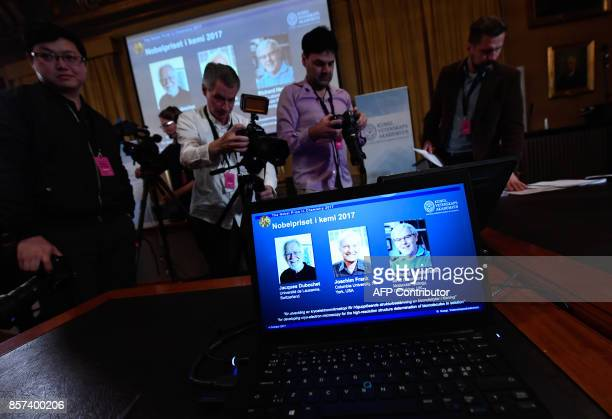 Journalists stand around a laptop screen displaying portraits of winners of the 2017 Nobel Prize in Chemistry on October 4 2017 at the Royal Swedish...