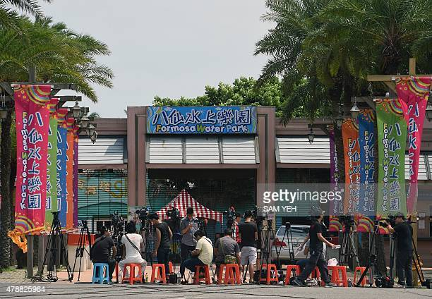 Journalists stand by the entrance of the water park in Pali district, in New Taipei City, on June 28, 2015. More than 500 people were injured, almost...