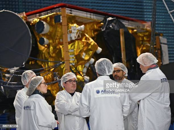 Journalists stand in front of the SES14 hybride 4ton satellite equipped with a plasma jet engine an electricallypowered propulsion system during a...