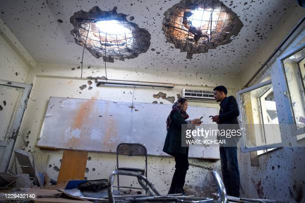Journalists stand inside of a damaged classroom at the National Legal Training centre a day after gunmen stormed the university in Kabul on November...