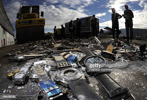 Journalists stand near counterfeit watches and goods crushed by a vibrating roller during an event to launch a new campaign by Swiss...