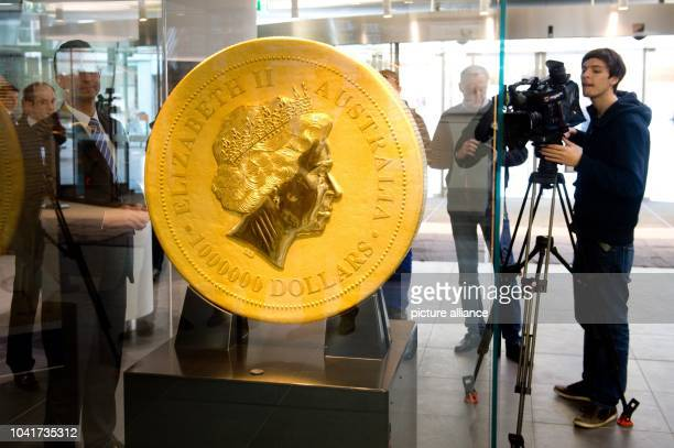 Journalists stand next to the world's biggest gold coin at the BadenWuerttembergische Bank in Stuttgart Germany 29 January 2014 The coin has a...