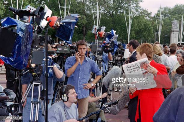 Journalists stand outside Buckingham Palace in London as people pay tribute to Diana, Princess of Wales on September 1, 1997.