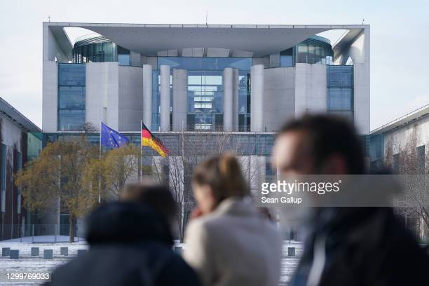 Journalists stand outside the Chancellery, where inside German Chancellor Angela Merkel was hosting a video summit between government and...
