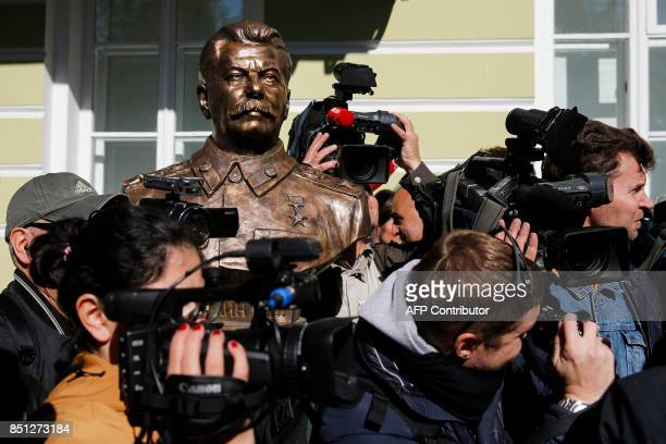Journalists surround a bust of Soviet leader Joseph Stalin during a ceremony unveiling a series of new sculptures of former top political figures at...