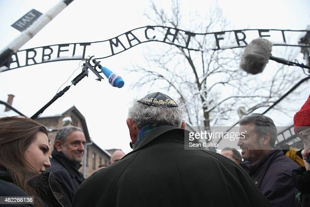 Journalists surround an Auschwitz survivor at the notorious 'Arbeit Macht Frei' entrance gate at the former Auschwitz I concentration camp which is...