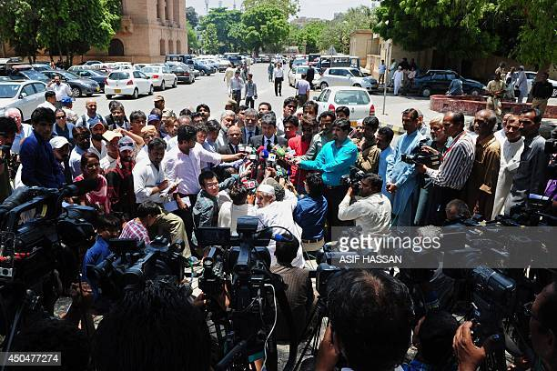 Journalists surround Farogh Naseem barrister and counsel for former Pakistani military ruler Pervez Musharraf as he speaks with media at the high...