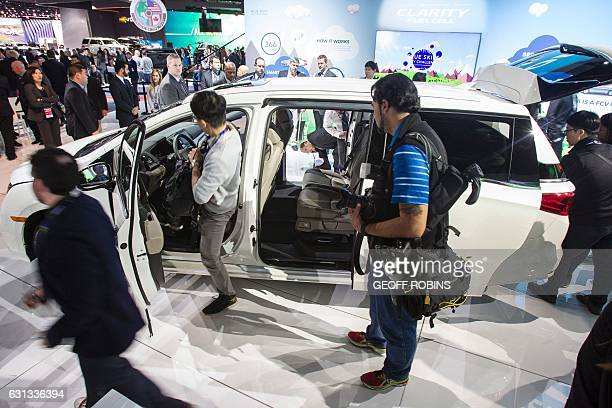 Journalists take a look at the 2018 Honda Odyssey during a press conference at the 2017 North American International Auto Show in Detroit Michigan...