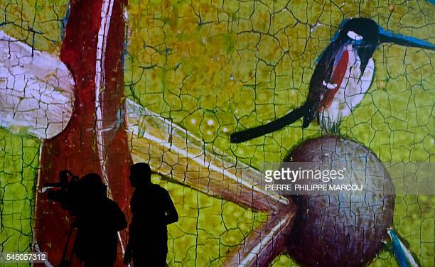 Journalists take images of a video installation on Dutch painter Hieronymus Bosch's masterpiece The Garden of Earthly Delights at El Prado museum in...