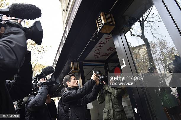 Journalists take pictures of a bullet hole in the window of a Japanese restaurant next to the cafe 'La Belle Equipe' at the Rue de Charonne in Paris...