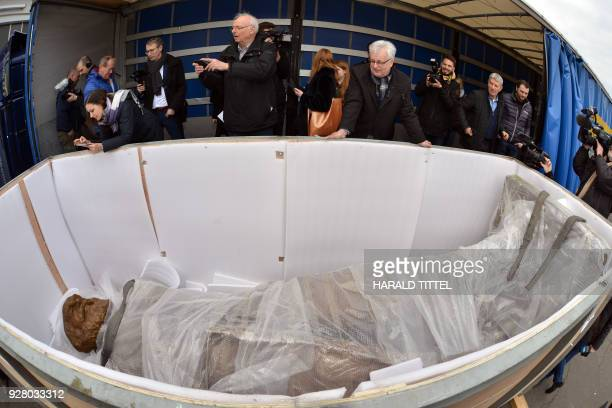 TOPSHOT Journalists take pictures of a statue of German philosopher economist political theorist and sociologist Karl Marx as it lays in its...