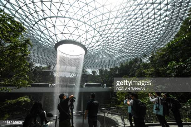 Journalists take pictures of the newly built Changi Jewel complex at the Changi international airport during a media preview in Singapore on April 11...