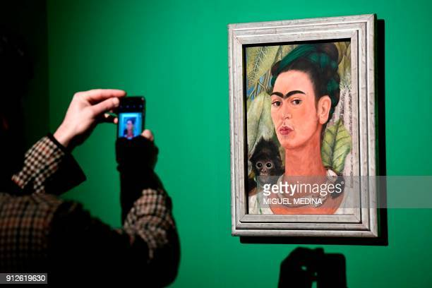 A journalists takes a picture of a painting by Mexican artist Frida Kahlo called Selfportrait with Monkey during a press visit to her exhibition...