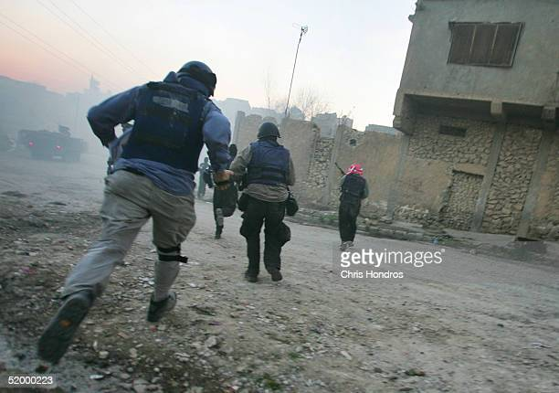 Journalists US troops and Iraqi police run for cover during a firefight with insurgents January 16 2005 in Tal Afar Iraq A routine patrol in the...