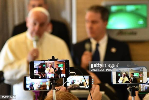 Journalists use their phones to record a video as Pope Francis delivers a press conference aboard the papal plane in Rome before departing to Chile...