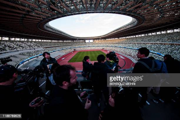 Journalists visit the National Stadium venue for the upcoming Tokyo 2020 Olympic Games during a media tour following the stadium's completion in...