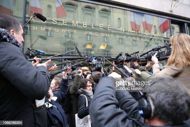 Journalists wait for French Prime Minister departure after he announced the suspension on rising fuel taxes to the LREM ruling party Members of...