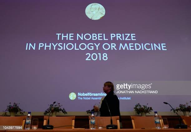 Journalists wait for the beginning of a press conference to announce the winner of the 2018 Nobel Prize in Physiology or Medicine at the Karolinska...