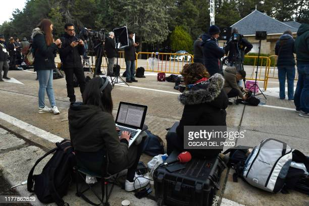Journalists wait for the exhumation of Spanish dictator Francisco Franco outside the Valle de los Caidos mausoleum in San Lorenzo del Escorial on...