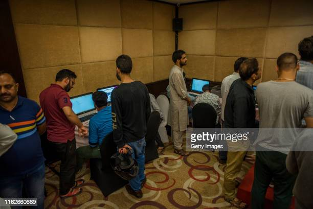 Journalists wait for their turn to use the only internet line connected with four computers, at a media center, on August 18, 2019 in Srinagar, the...