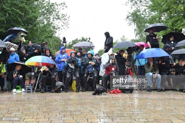 Journalists wait in the rain near the Festival Theatre on July 25 in Bayreuth southern Germany ahead of the opening of Bayreuth's legendary annual...