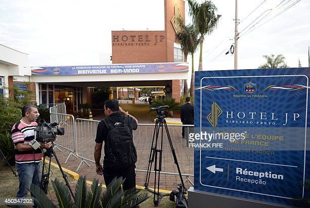 Journalists wait on June 9, 2014 in Ribeirao Preto in front of the entrance of the JP Hotel which will host the French national football team during...