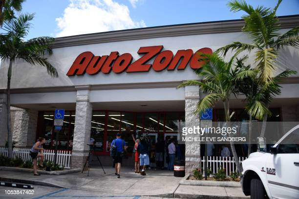 Journalists wait outside as FBI agents search for clues and evidences at the Auto Zone Store in Plantation North of Miami on October 26 2018 where a...