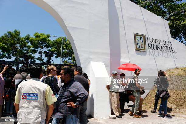 Journalists wait outside the Municipal Funeral Home during the funeral of Óscar Alberto Martínez Ramírez and his daughter Valeria at San Romero...