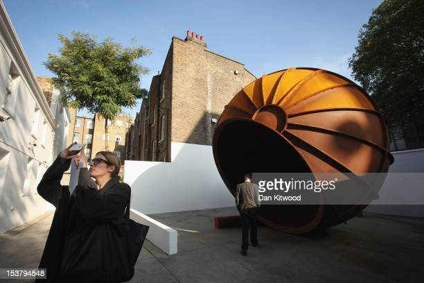 Journalists walk around a piece of work entitled 'Intersection' by artist Anish Kapoor during a press preview at the Lisson Gallery on October 9 2012...
