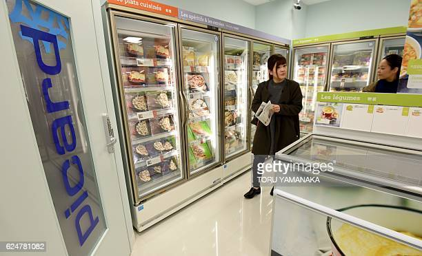 Journalists walk around a store of French frozen food brand Picard during a press preview in Tokyo on November 21 2016 Picard will open the first...