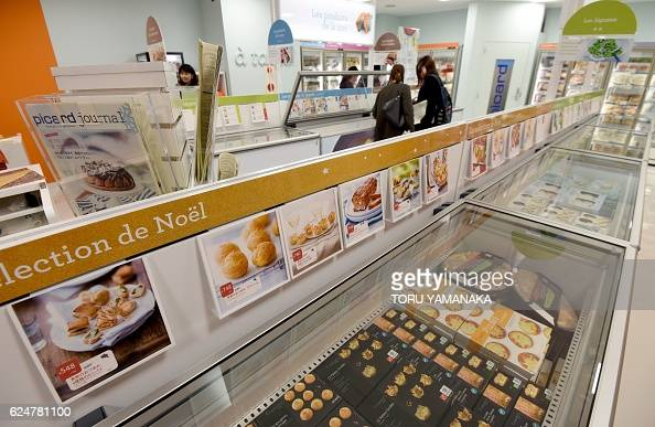 Journalists walk around a store of French frozen food ...