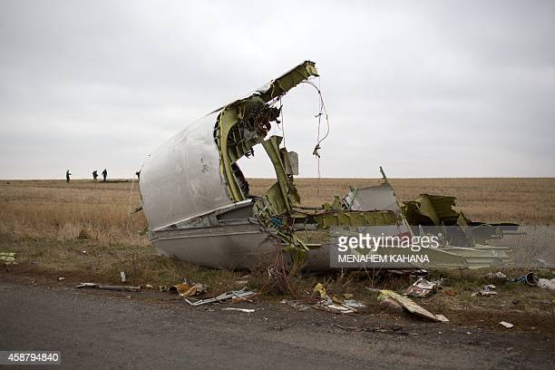 Journalists walk behind parts of the Malaysia Airlines plane Flight MH17 as Dutch investigators arrive near at the crash site near the Grabove...