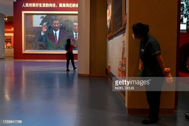Journalists walk past a screen showing video footage of Chinese President Xi Jinping, during a visit to the Museum of the Communist Party of China,...