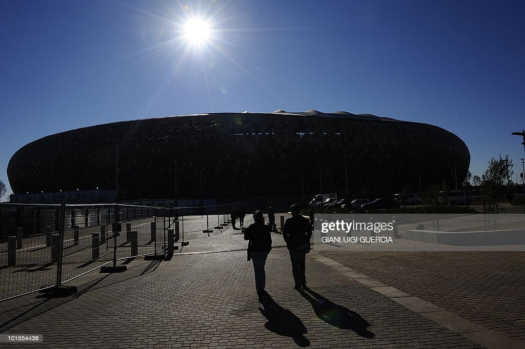 Journalists walk towards Soccer City stadium on June 2, 2010 as they attend the official handing over of the Soccer city stadium to FIFA ahead of the FIFA WC2010 that will take place in South Africa from the 11 of June to the 11 of July, in Johannesburg, South Africa.